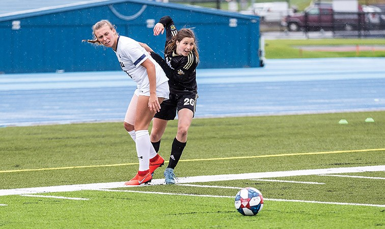 UNBC Timberwolves forward Sofia Jones eyes up the loose ball while dodging a Mount Royal University Cougars defender on Sunday afternoon at Masich Place Stadium. Citizen Photo by James Doyle