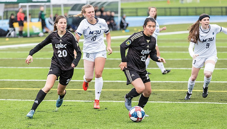 UNBC Timberwolves ball carrier Jenna Wild leads a rush with Sofia Jones (20) as she dribbles the ball ahead of the Mount Royal University Cougars Emily Wiltshire (10) and Quinn Hardstaff (9) Sunday afternoon at Masich Place Stadium. The teams played to a scoreless draw.