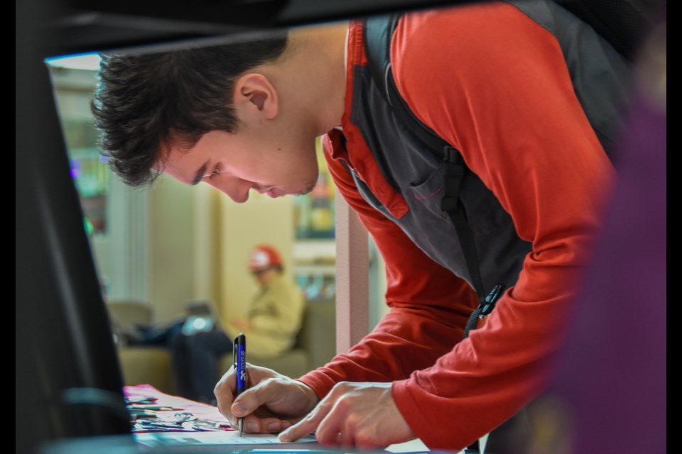 Douglas College student Jonah Roesler, 22, signs a pledge to vote in the upcoming federal election