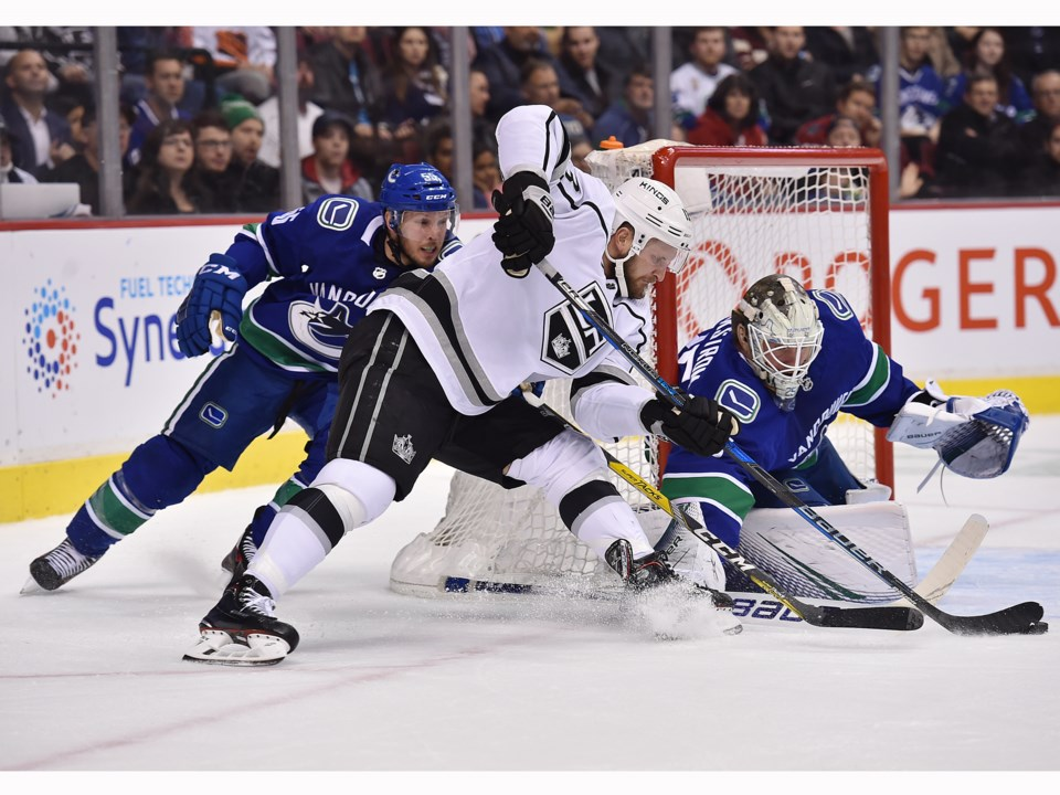 Kyle Clifford of the Los Angeles Kings tries to jam a puck past Jacob Markstrom of the Canucks.
