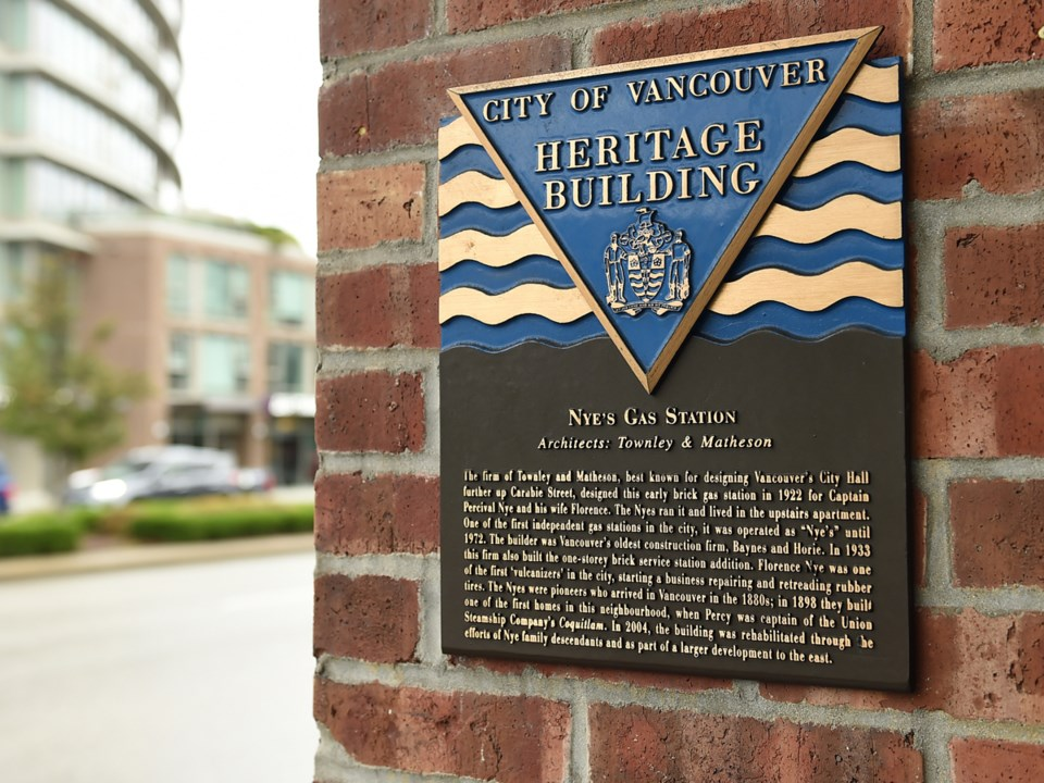 A plaque indicates a building is protected by municipal heritage designations or a legal agreement.