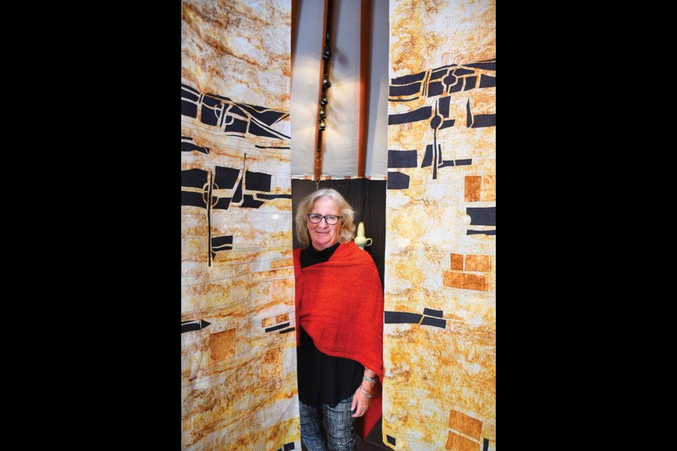 Catherine Nicholls is framed by part of her treated fabric installation,A Landscape of Exhaustion and Moral Decay.