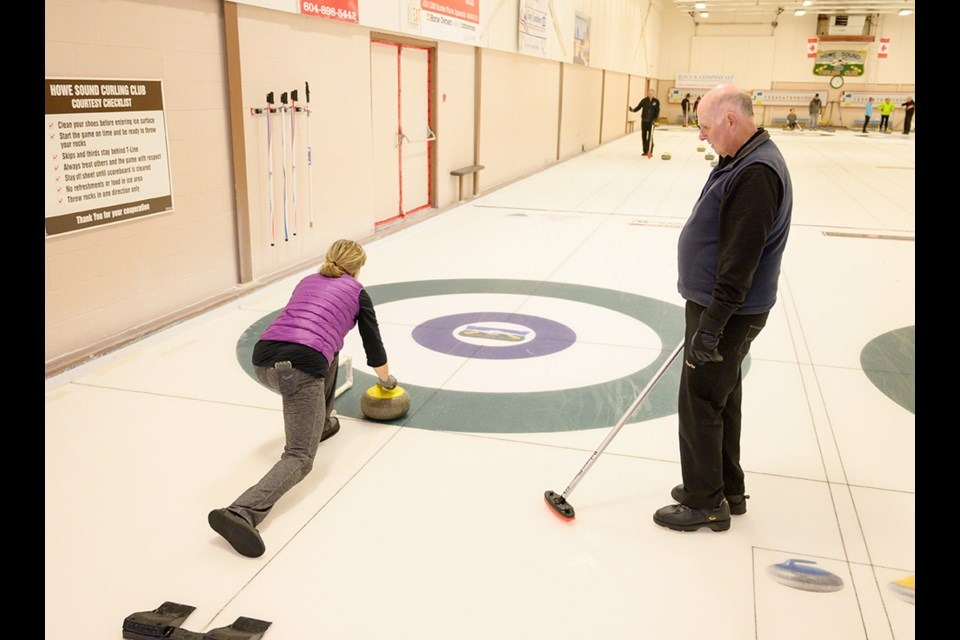 First time curler Kathy Malvern gets some instruction from Ken Taylor.