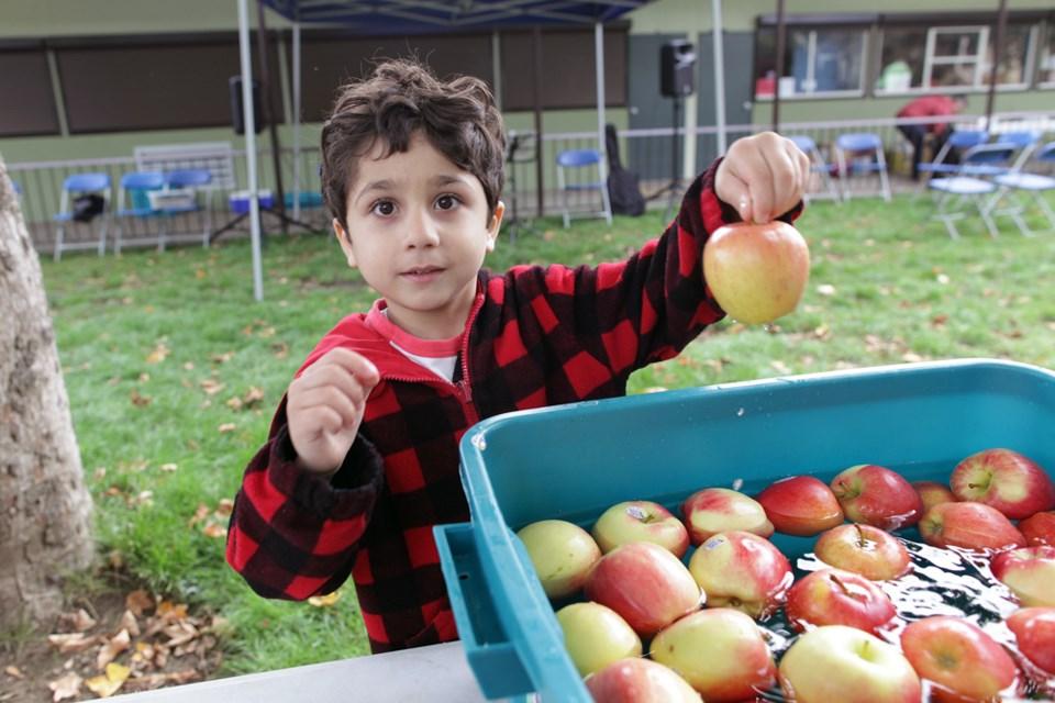 Karos Karem, 5, picks an apple out of the apple wash.