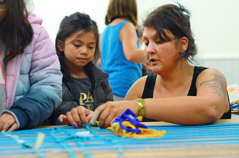 Semiahmoo artist and cultural historian Roxanne Charles helps Cascade Heights Elementary student Phoebe Doctor weave with recycled materials at the inaugural Indigenous Week of Learning at Burnaby Village Museum Tuesday.