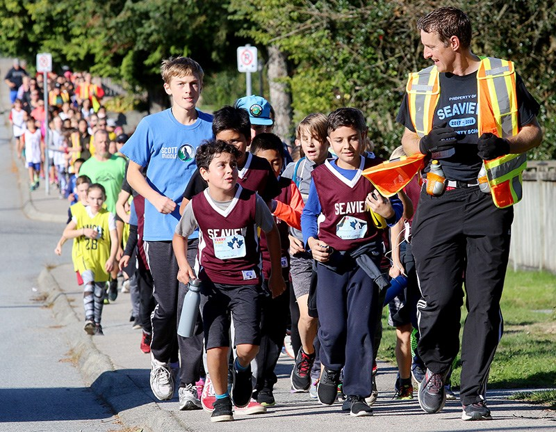 Led by Frank Pearse, the principal at Seaview elementary school in Port Moody, students from several Tri-City schools run to assemble at the office of the Terry Fox Foundation, where they donated more than $70,000 for cancer research last Friday.