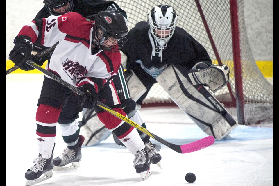 Richmond Ravens' Ashley Specht battles in front of the Sherwood Park net during round-robin action Saturday at the Seventh Annual Pacific Coast Female Rep Hockey Classic. The hosts won this game 3-1 and went on to capture the Midget Division title with a perfect five-game run.