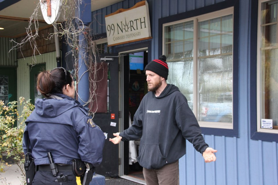 Bryan Raiser speaks with an RCMP officer as his store, 99 North, is closed in Squamish on Nov. 5.