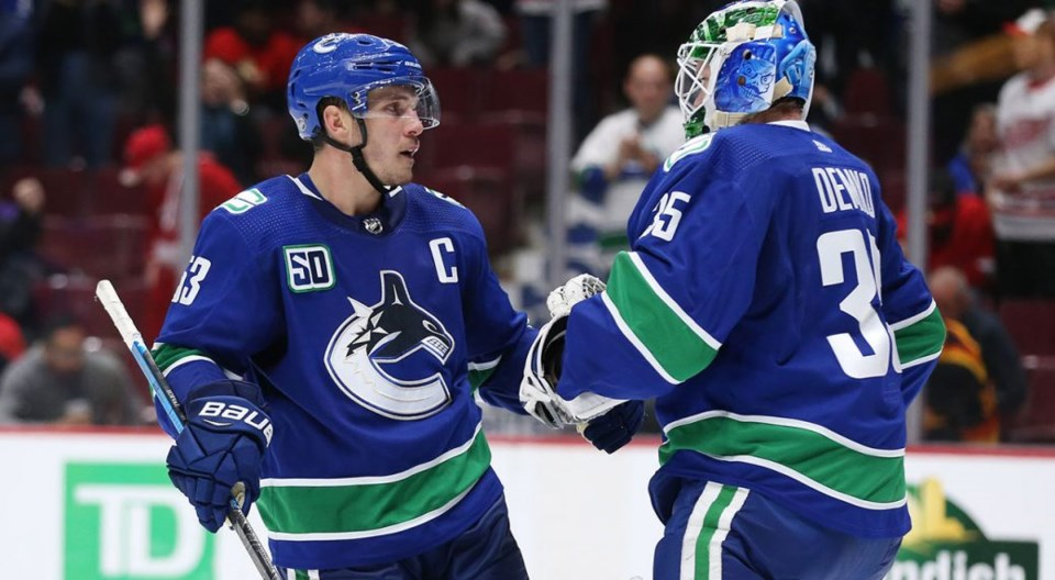 Bo Horvat congratulates Thatcher Demko on a win for the Vancouver Canucks.
