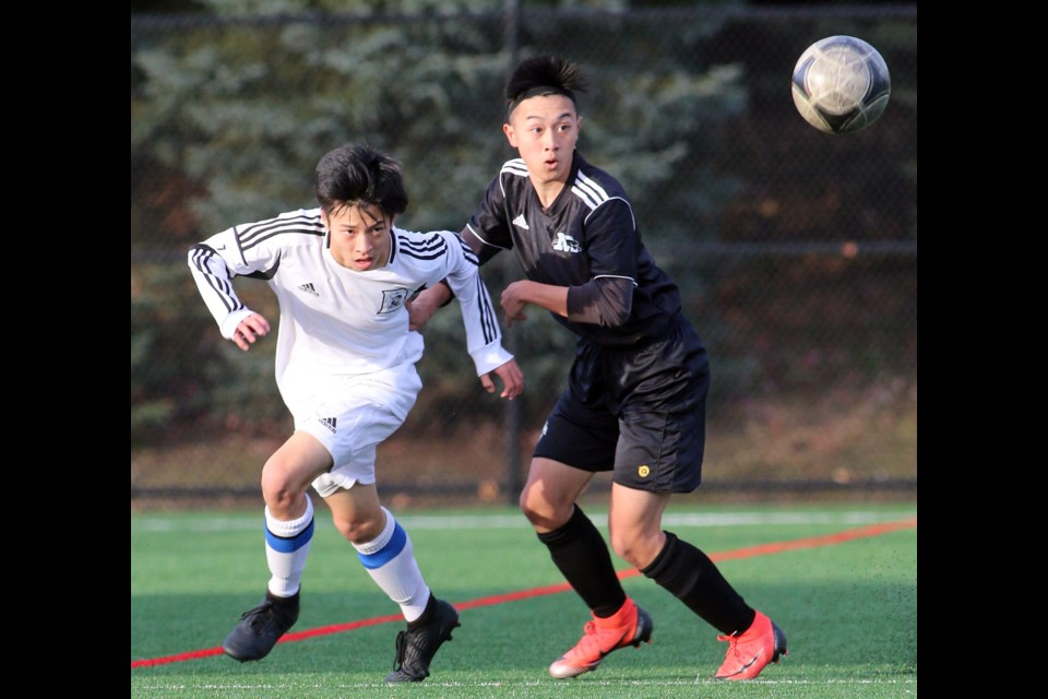 Michael Cho, of the Dr. Charles Best Blue Devils and Moscrop Panthers' Edison Phung keep their eye on the ball in the first half of their Fraser North Athletic Association AAA senior boys soccer district final, last Thursday at Coquitlam's Town Centre Park. Moscrop won, 4-1. Both teams advance to the provincial championships that will be played in Burnaby beginning Nov. 21.
