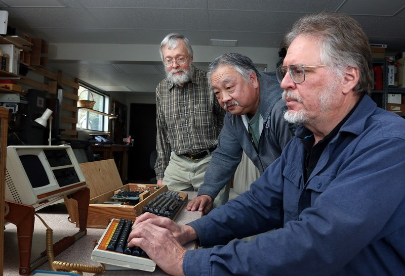 David Querbach sits at his old Orotona Attaché portable computer in the workshop of his Port Moody home, while former colleagues from the West Coast Computer Society, Al Mar and Dave Wiens, wonder if it will boot up. Members of the society, the first of its kind that formed in the Lower Mainland, in 1976, are holding a reunion in Coquitlam on Saturday.