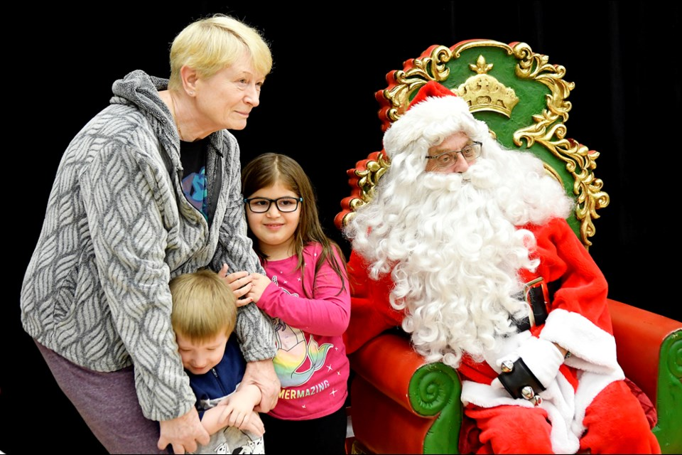 Helena Perry, six-year-old Sophie and three-year-old Cole visit with Santa.