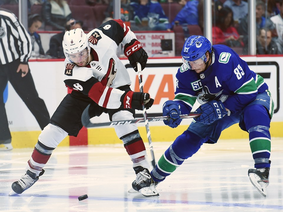 The Vancouver Canucks' Jay Beagle battles for the puck with the Arizona Coyotes' Nick Schmaltz.