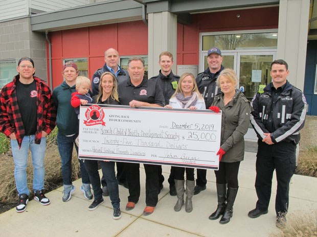 Members of the Delta Firefighters Charitable Society present a cheque for $25,000 to Reach Child & Youth Development Society.