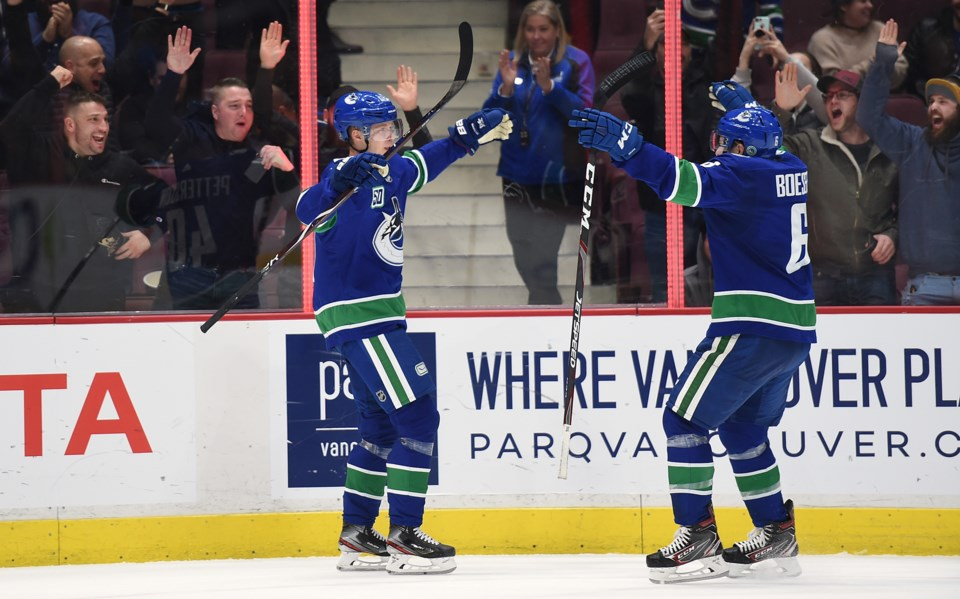 Elias Pettersson and Brock Boeser celebrate an overtime game-winning goal.