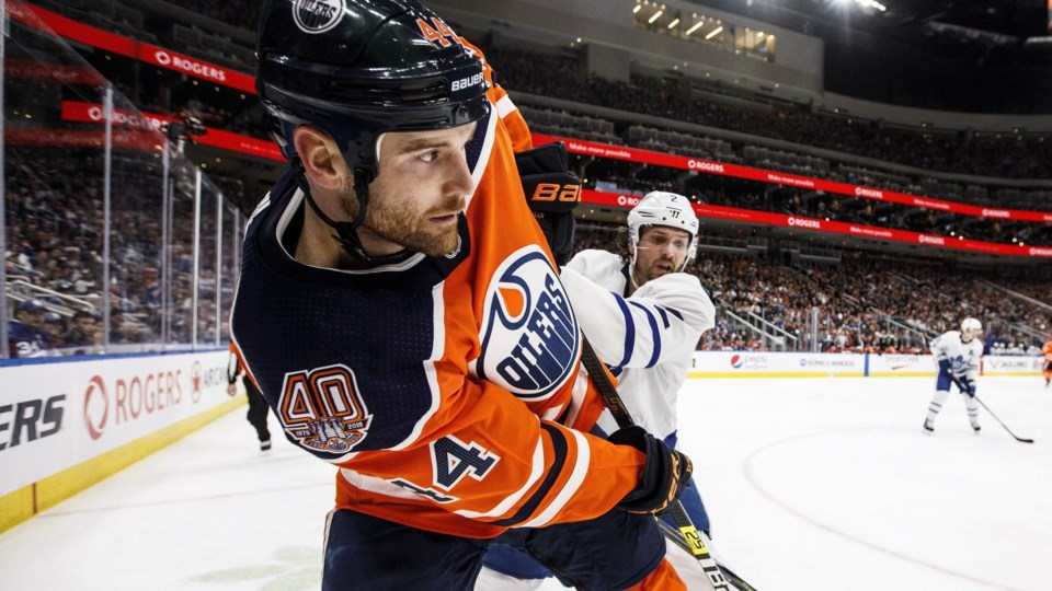 Zack Kassian plays the puck along the boards.
