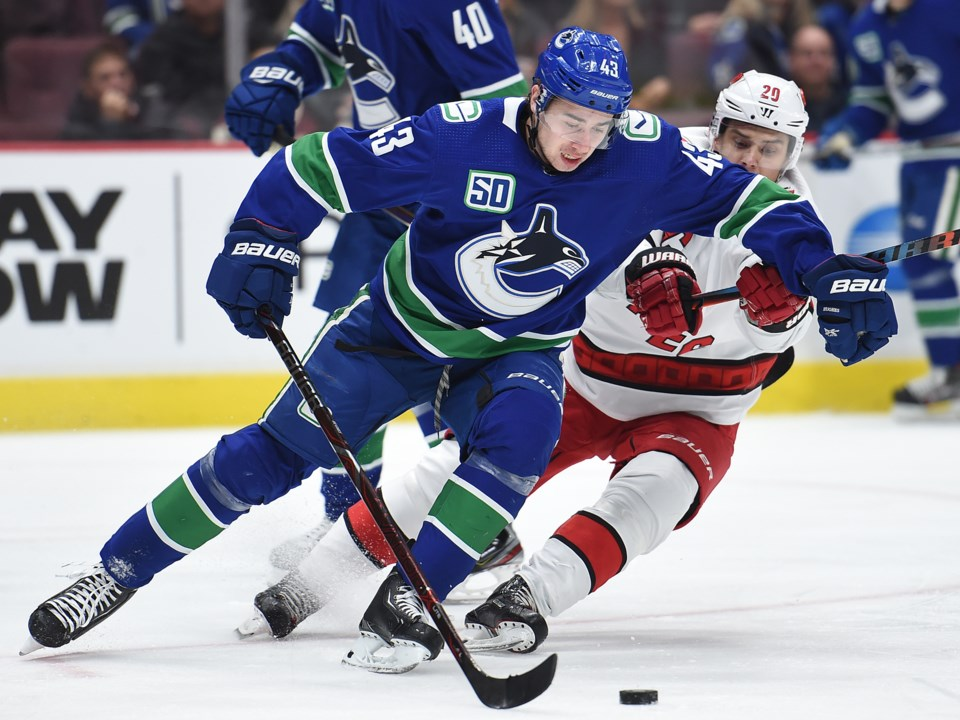 Quinn Hughes protects the puck from Sebastian Aho of the Carolina Hurricanes.