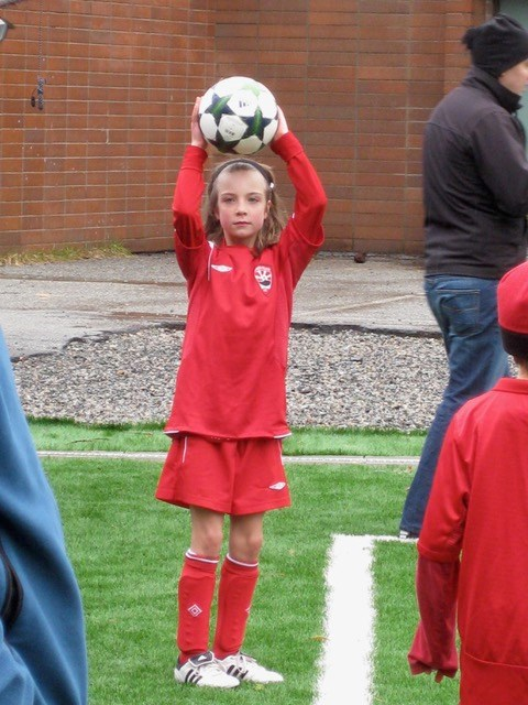Molly as a young girl in a red jersey and shorts doing a throw-in.