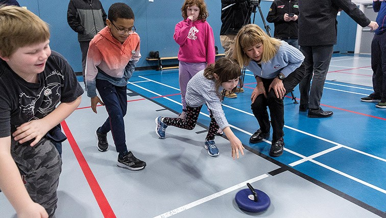 Citizen Photo by James Doyle. Olympic curler Karri Willms helps the kids do some floor curling at Harwin Elementary School during a learn-to-curl session on Friday morning.