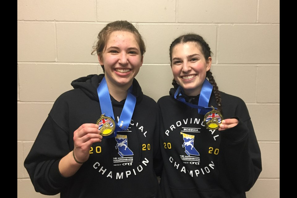 St. Thomas More medalists Logan Stimson, at left, and Clara Scaglione celebrate their championship gold wins at last week's B.C. Secondary Schools wrestling championships in Langley.