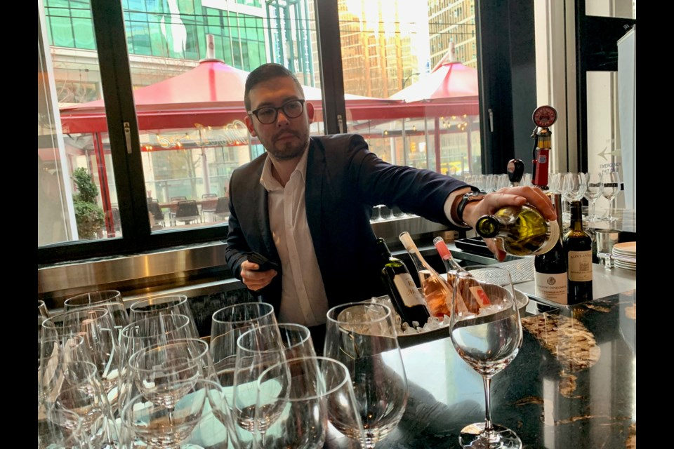 Sommelier Jason Yamasaki pouring wine at the festival opening.