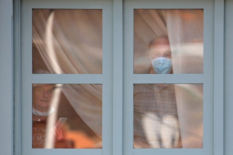 People look through a window of the H10 Costa Adeje Palace hotel in La Caleta while under lock down