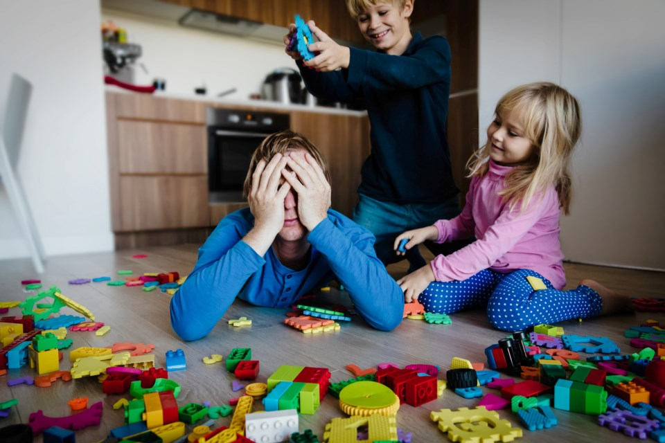 tired parent surrounded by children with toys