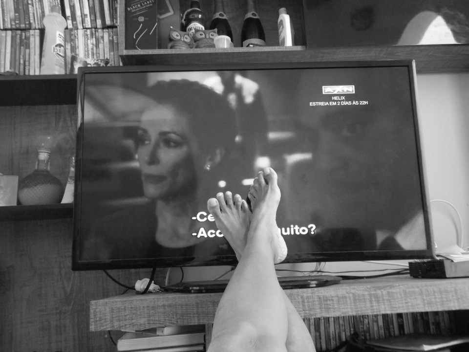 Black and white photo of feet propped up on table with TV in background