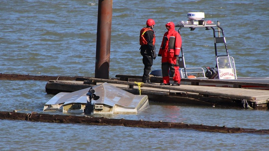 Search and Rescue crews from Coquitlam stand next to a capsized boat on the Pitt River.