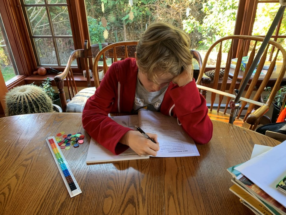 A boy sitting at a kitchen table working on schoolwork