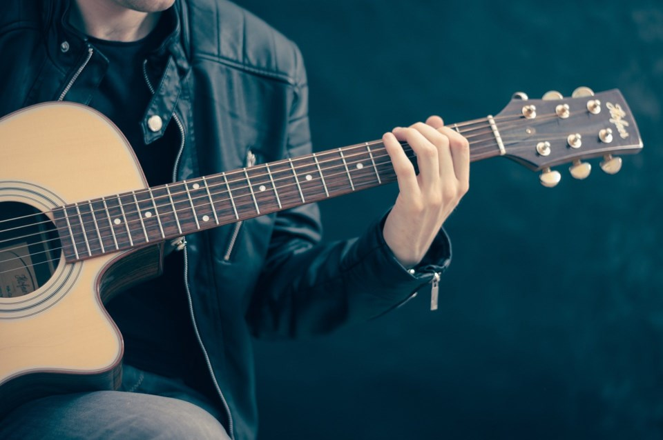 Fellow playing the guitar with a black background