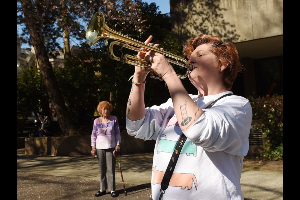 Samantha Monckton plays her trumpet Wednesday in front of her father's long-term care home, as resident Margaret Holtz looks on. Monckton's father, Garry, has tested positive for COVID-19. Photo Dan Toulgoet