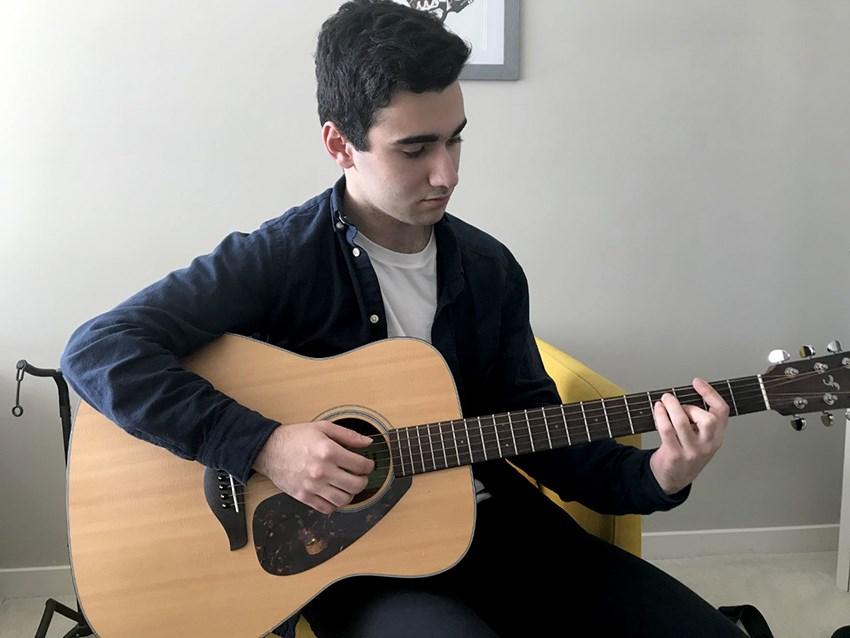 Student practices guitar during COVID-19 quarantine