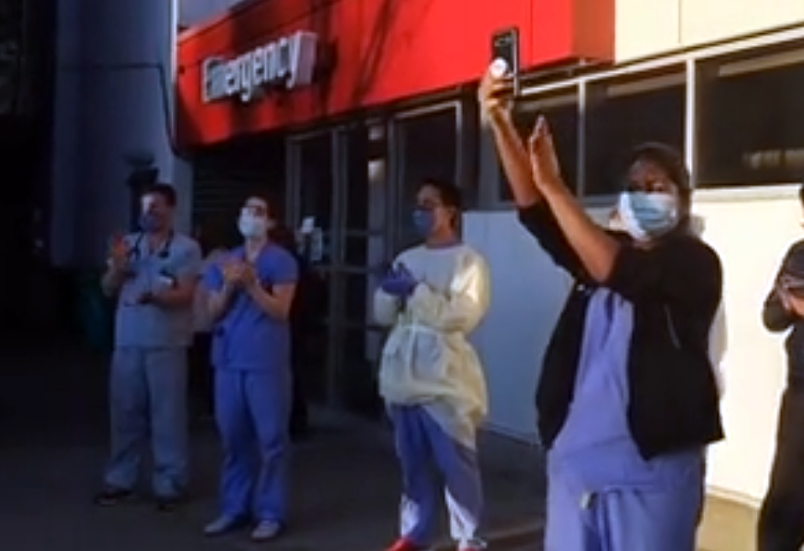 Front-line health-care workers at Burnaby Hospital respond to a salute from police, firefighters and paramedics Wednesday in a screen grab from a video posted on social media. Residents in Coquitlam are also being asked to participate in a nightly cheer during the 7 p.m. shift change at hospitals and health care facilities.