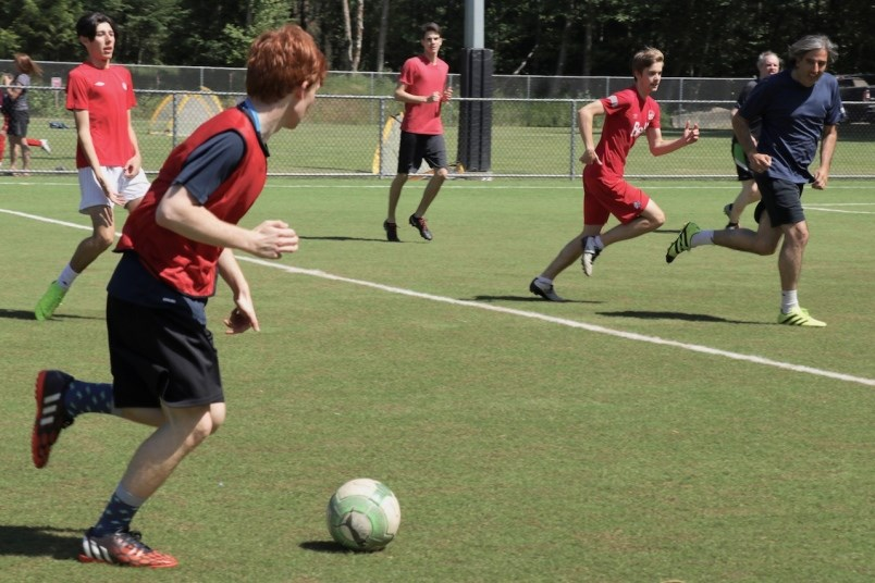 Youth playing soccer on turf field