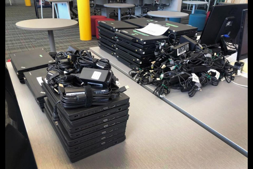 Stacks of laptops are ready to be loaned out at a school district site.