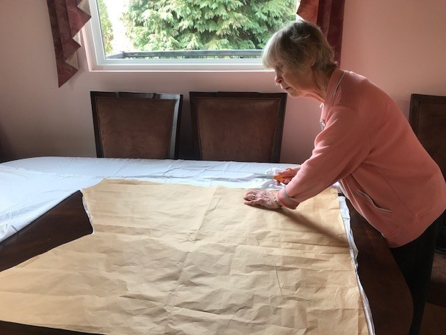 A volunteer cuts fabric for one of the gowns in the Dress the Docs
