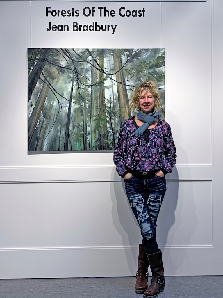 Jami Scheffer standing before a painting in the gallery