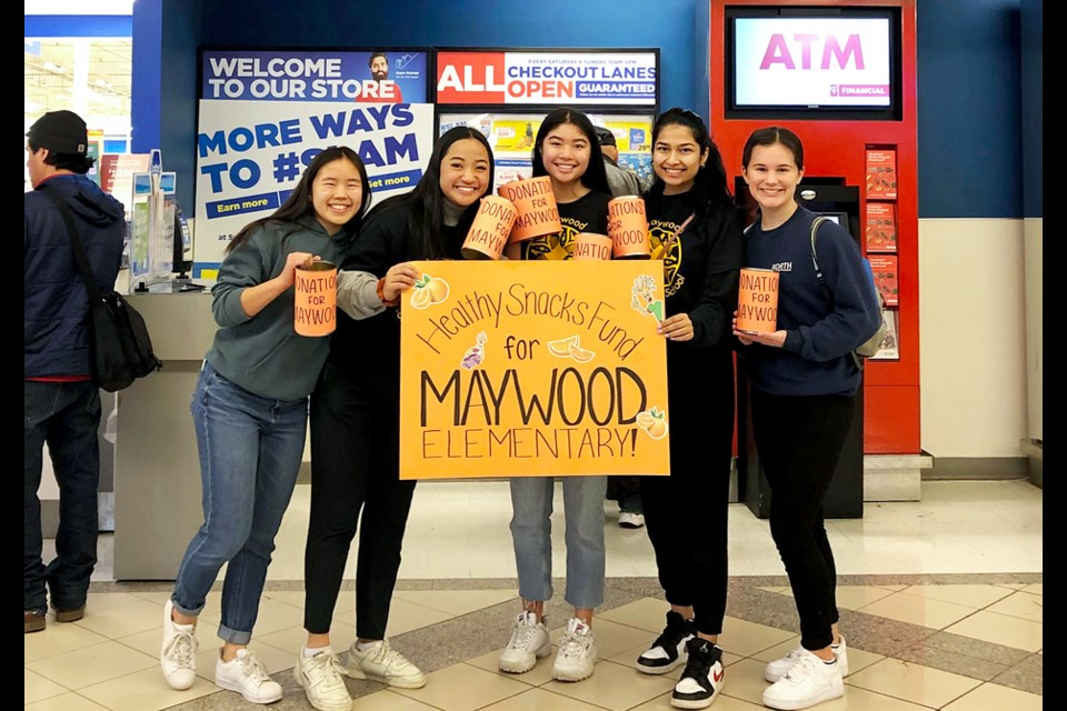 Burnaby North Secondary School Grade 12 students Haley Ham, Elizabeth Chung, Megan Wong, Avneet Minhas and Cassandra Sacilotto pose for a photo at the entrance of the Metrotown Superstore, where they bagged groceries to fundraise for healthy snacks for local elementary school kids.