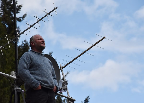 Scott Tilley looks in the direction of the LES-5, next to the antenna he constructed and installed on the roof of his home in Roberts Creek.