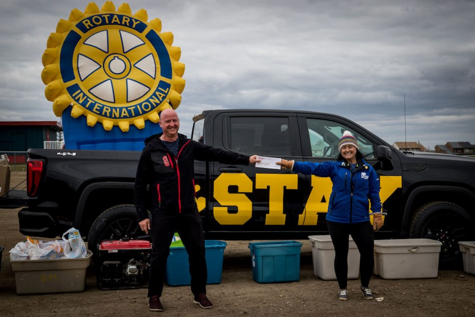 Shane Stirling of Epscan hands a donation to Rotarian Samantha Warren at the Mother's Day drive-thru fundraiser held at the Surerus ball diamonds, May 10, 2020.