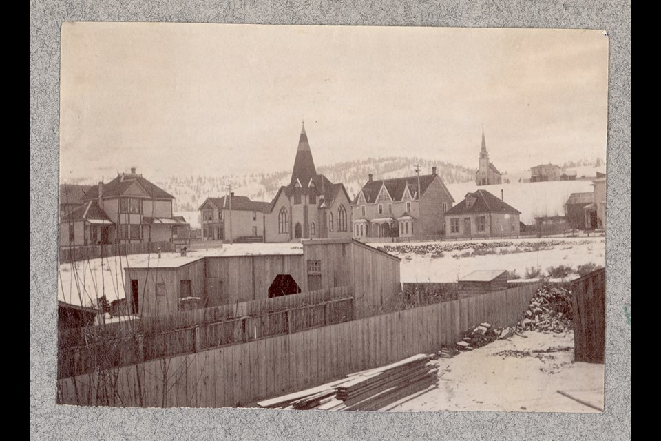 A photo taken from back of Gordon's Store, with the Presbyterian church in the foreground and the Roman Catholic Church on the hill in background, ca. 1898.