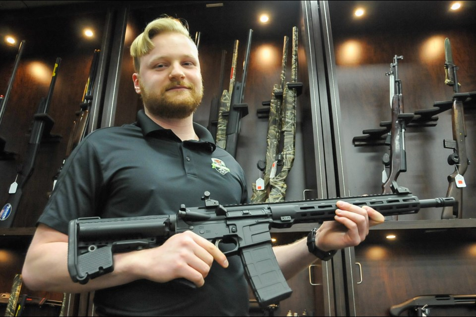 Assistant manager of Tiger Arms, Josh Faber, displays one of dozens of AR-15 variants his store has been sitting on with since they were banned with roughly 1,500 other guns May 1. Now he says RCMP are quietly adding more to that list.