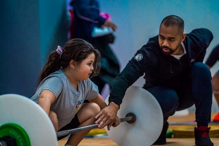 A coach helps a girl train at Engineered Bodies in Port Moody. It was the first gym in the Lower Mai
