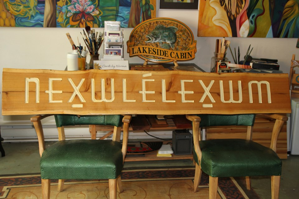 Wooden sign propped up on two chairs