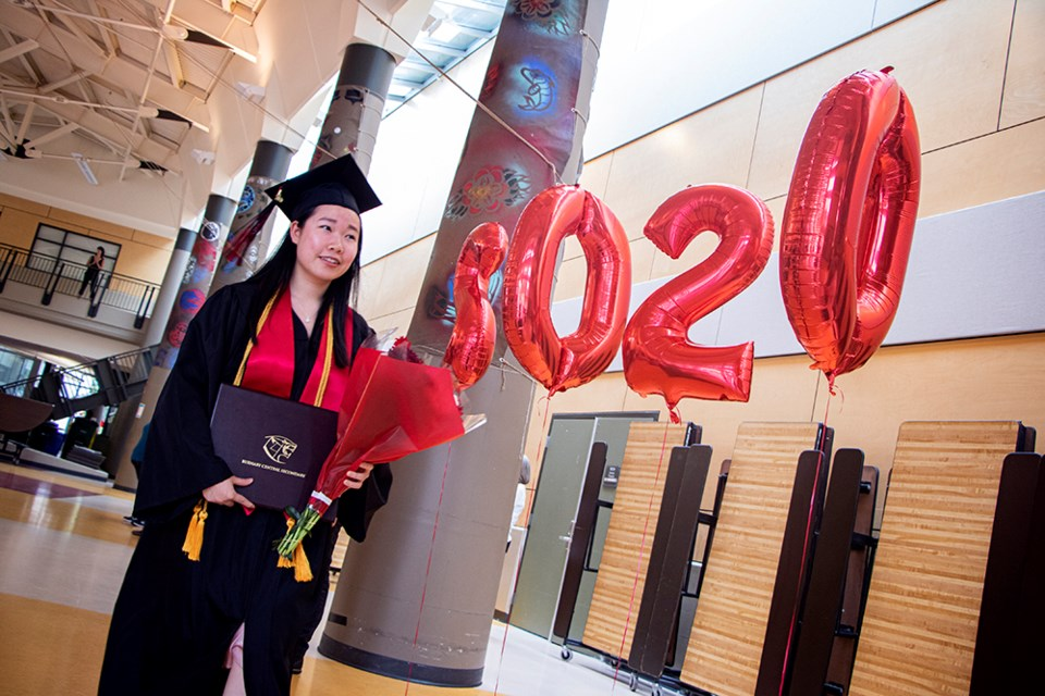 "Ellie Li walks past a set of balloons that read ""2020"" after posing for photos on stage with Burnaby Central Secondary principal Dianne Carr during the school's grad ceremony."