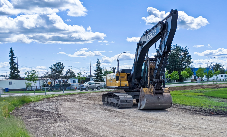 An operator waits for a new load of gravel during construction of an elevated base at the Bert Bowes outdoor track on June 26, 2020.
