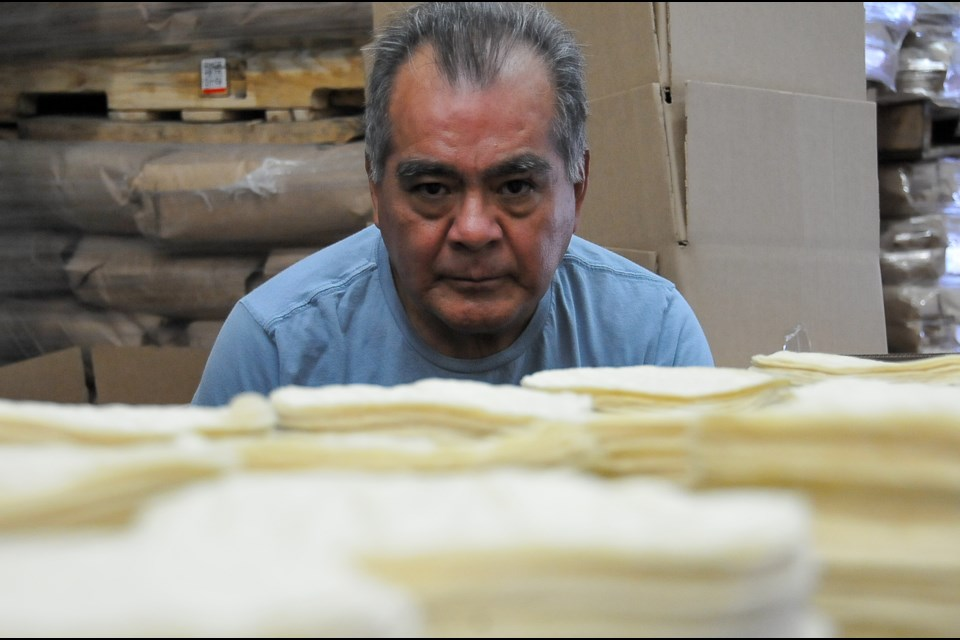 Carlos Hernandez checks on stacks of corn tortillas as they roll off the assembly line at his Santa Rosa factory in Port Coquitlam.