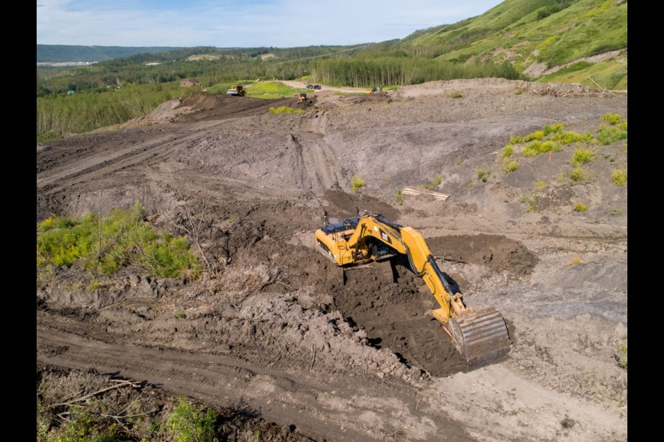 Crews build a temporary access road through the Old Fort landslide, July 8, 2020.