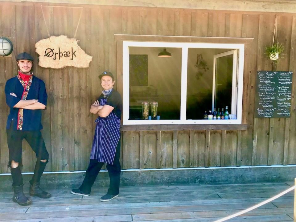 Chefs Jak Hedley and Matt Matheson leanign against a building